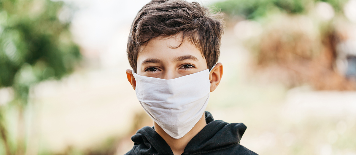 Portrait of 10 year old boy wearing homemade protective mask sunning during quarantine. Coronavirus, Covid-19 and pandemic concept